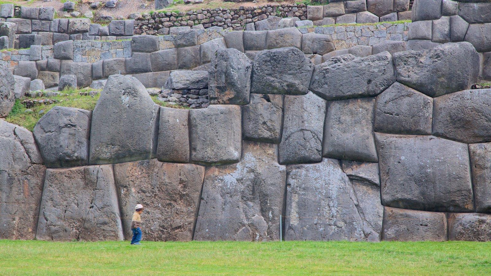 Sacsayhuaman mostrando elementos de patrimônio e uma ruína assim como uma criança sozinha