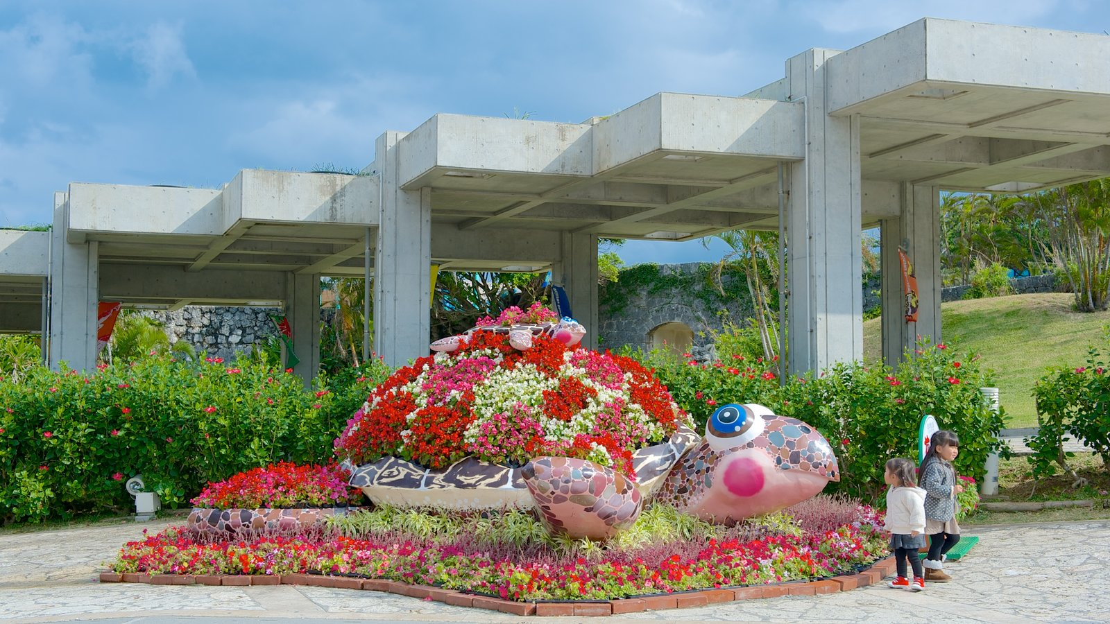 Okinawa Churaumi Aquarium which includes a garden, outdoor art and flowers