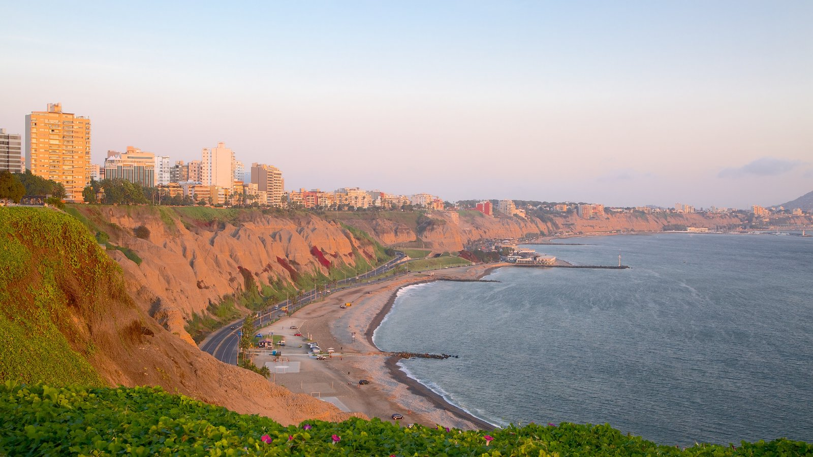 Lima featuring a sandy beach, landscape views and a sunset