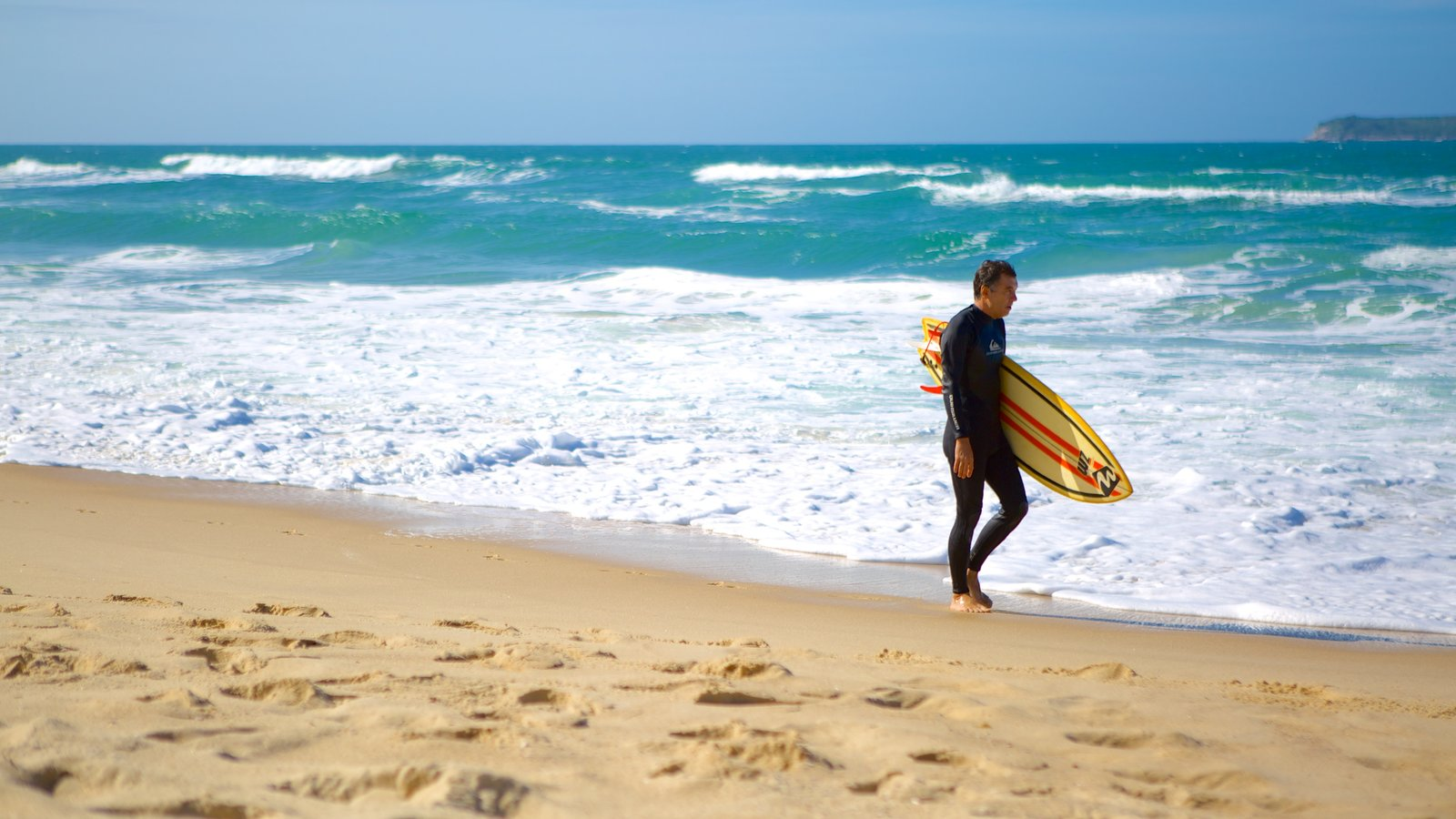 Praia Mole que inclui surfe e uma praia assim como um homem sozinho