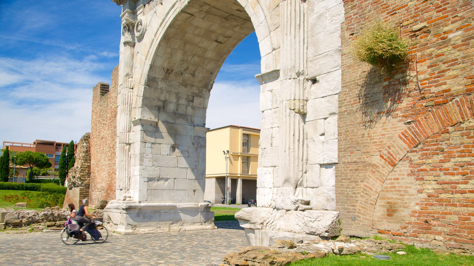 Arco de Augusto mostrando elementos de patrimônio e uma ruína