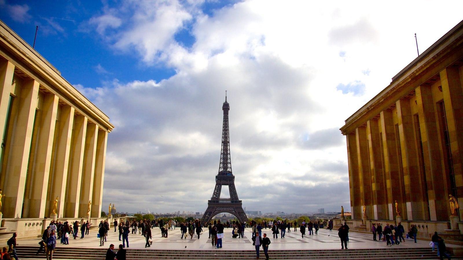 Torre Eiffel caracterizando um monumento e uma praça ou plaza assim como um grande grupo de pessoas