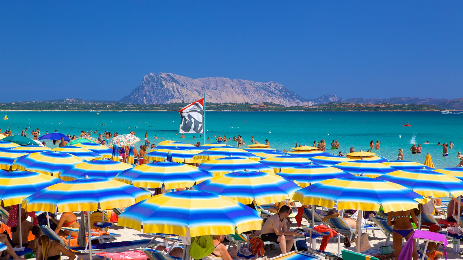 San Teodoro featuring a sandy beach and general coastal views as well as a large group of people