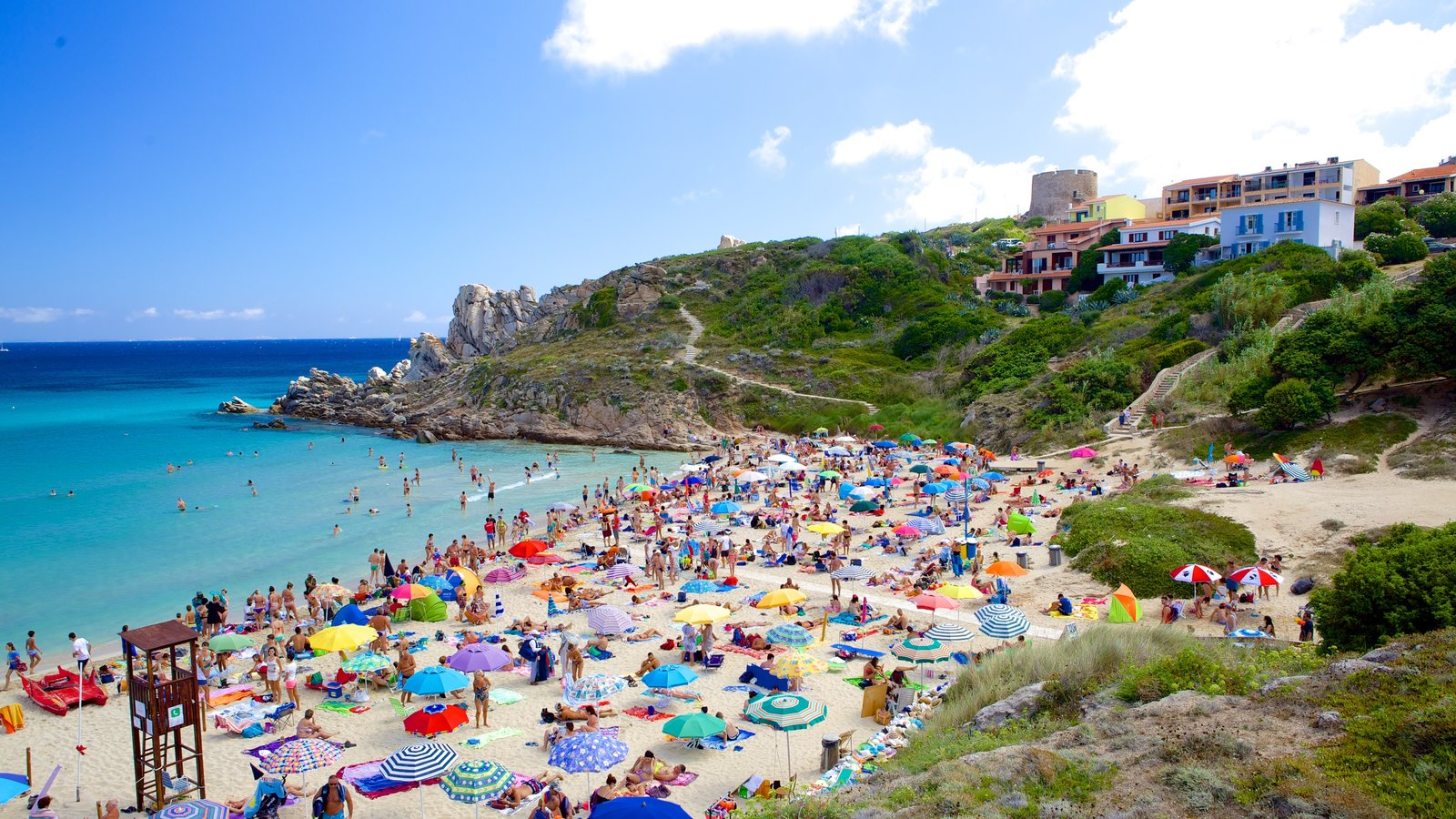 Santa Teresa di Gallura featuring a sandy beach as well as a large group of people