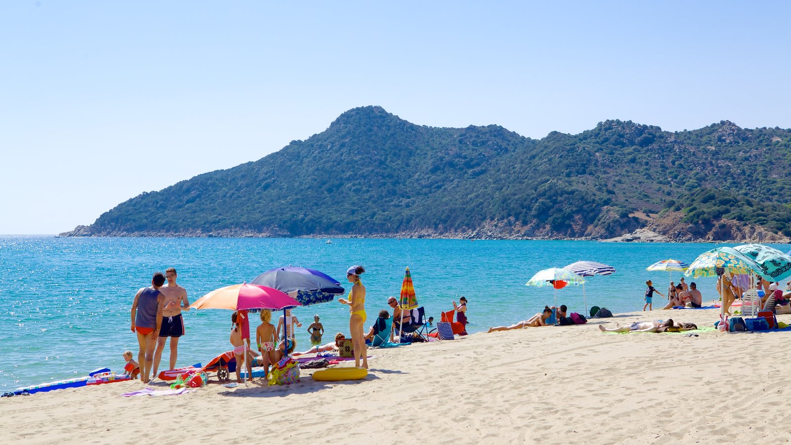 Cala Sinzias which includes a sandy beach as well as a large group of people