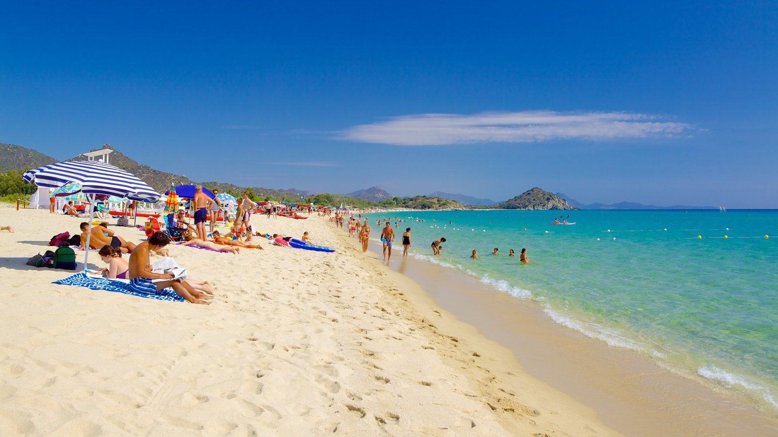 Cala Sinzias featuring a sandy beach as well as a large group of people