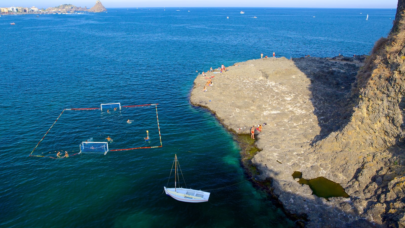 Aci Castello showing rocky coastline and watersports