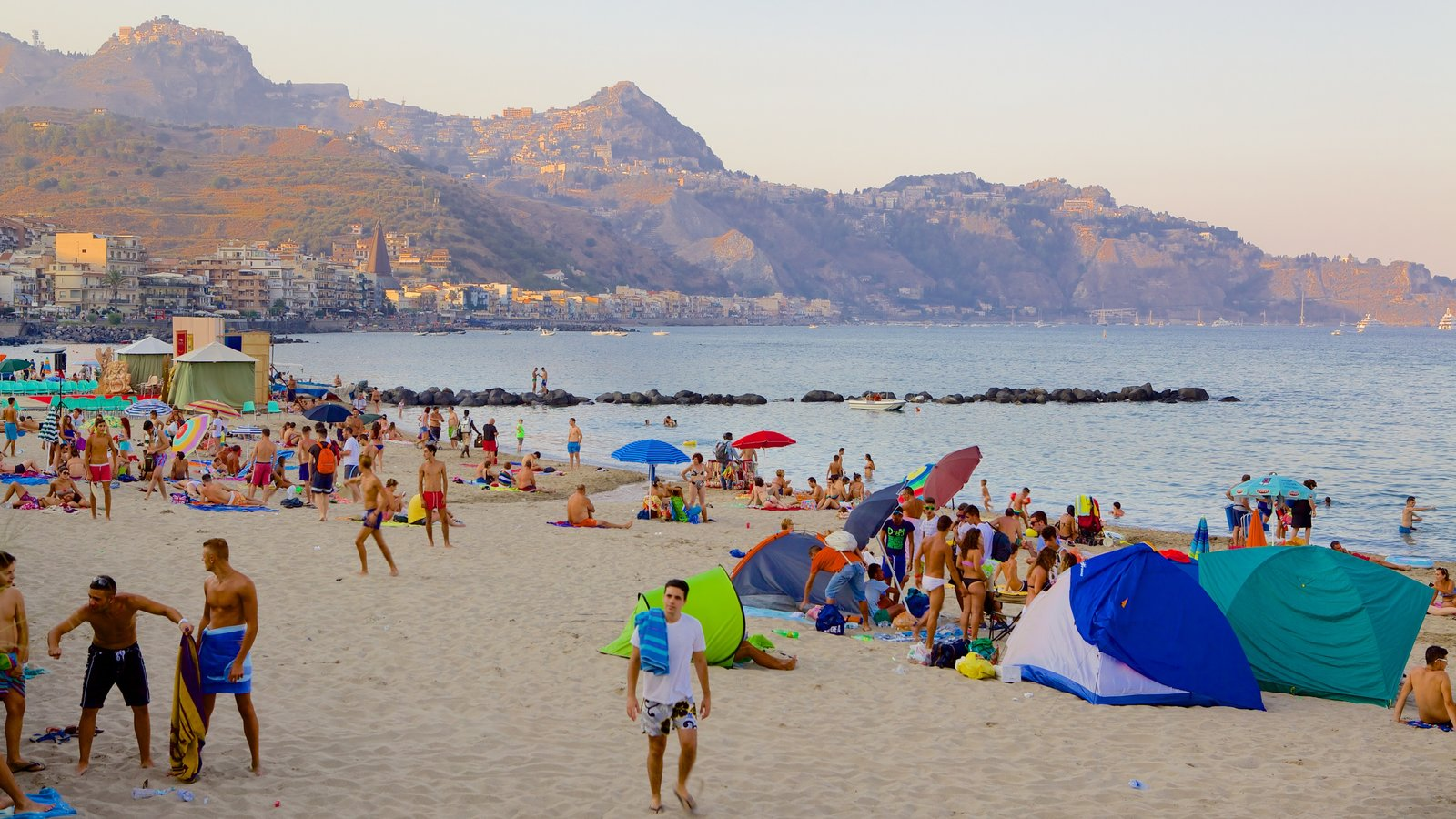 Giardini Naxos which includes a beach as well as a large group of people