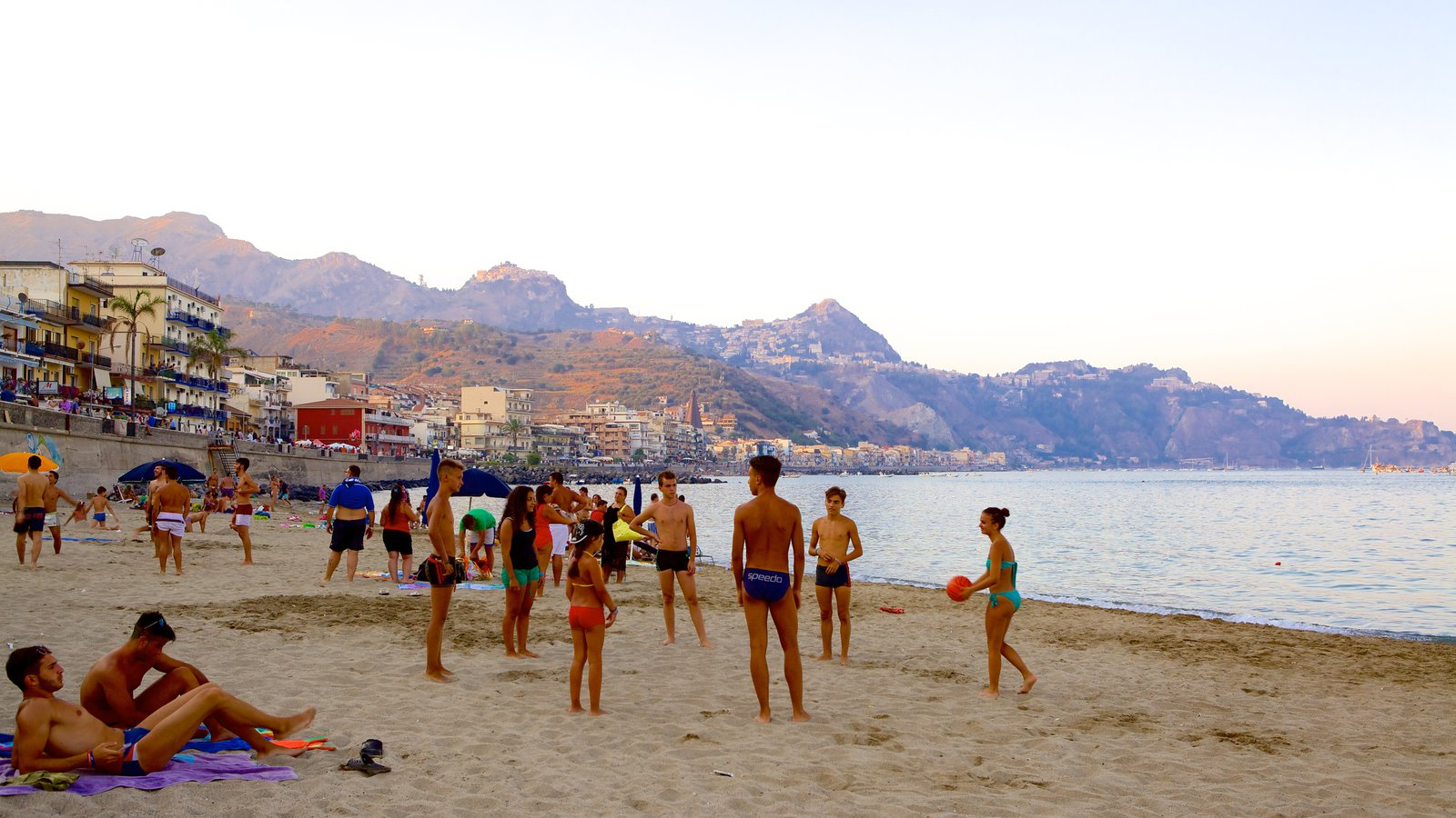Giardini Naxos featuring a sandy beach as well as a large group of people