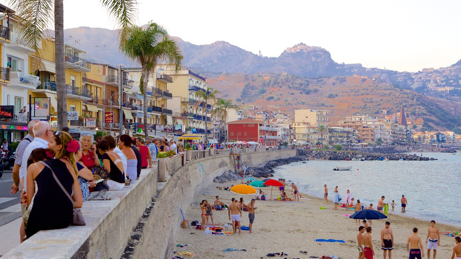 Giardini Naxos which includes a sandy beach and a coastal town as well as a large group of people