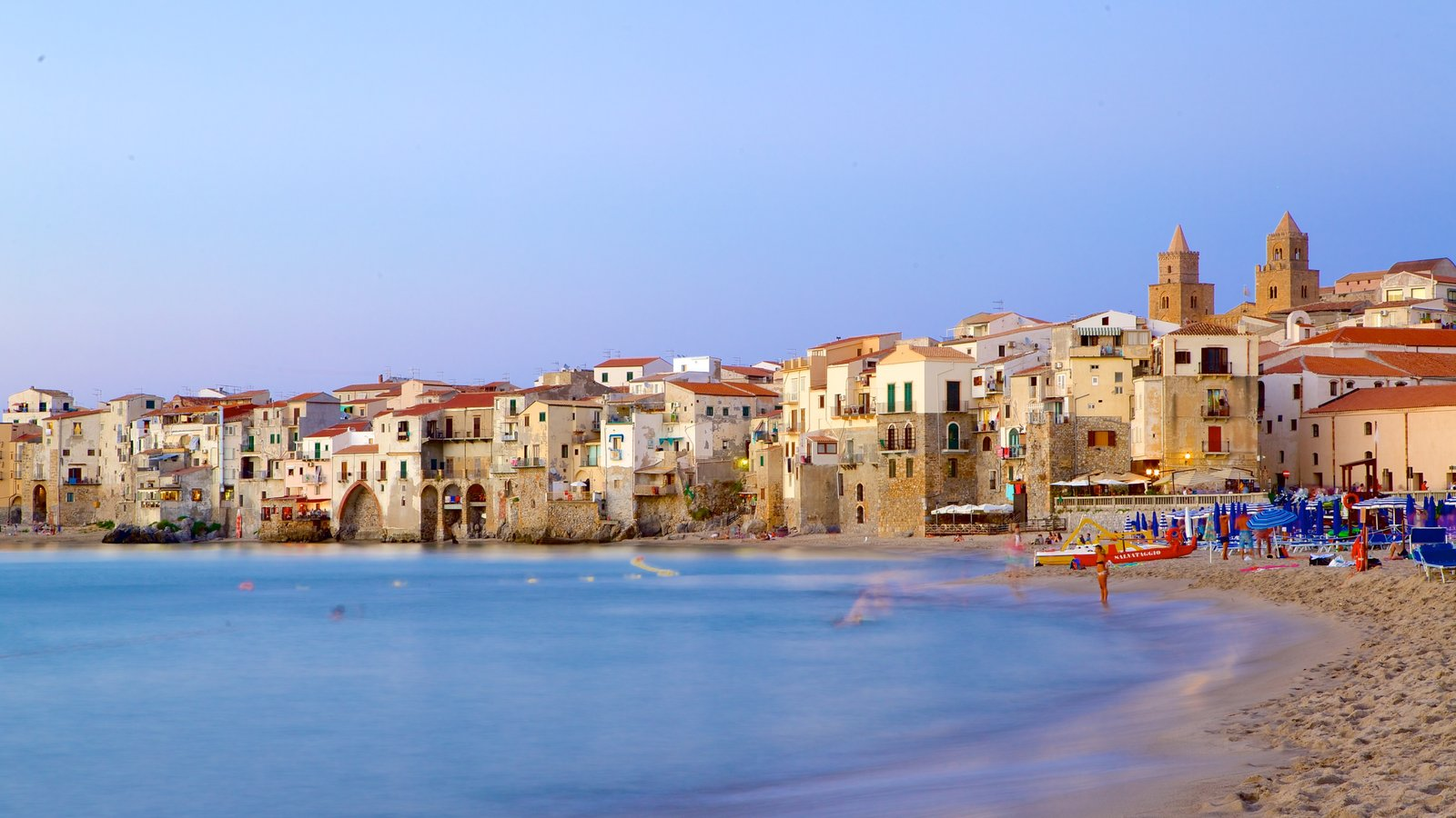 Cefalu showing a sandy beach and a coastal town