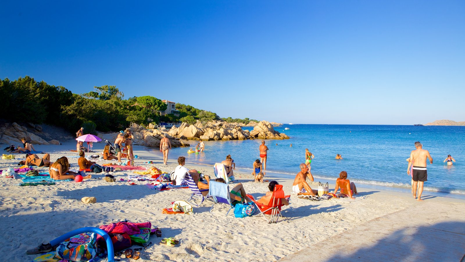 Capriccioli Beach which includes tropical scenes, a beach and a coastal town