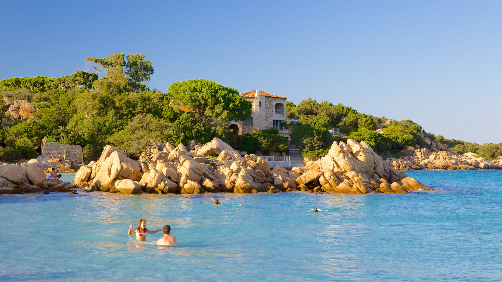 Capriccioli Beach showing a coastal town, rugged coastline and landscape views
