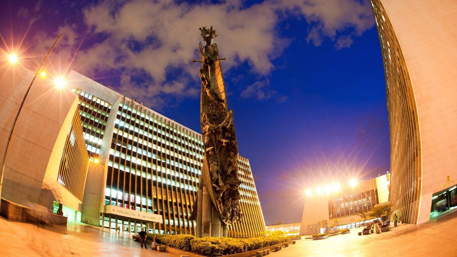 Medellín caracterizando uma praça ou plaza, uma estátua ou escultura e cenas noturnas