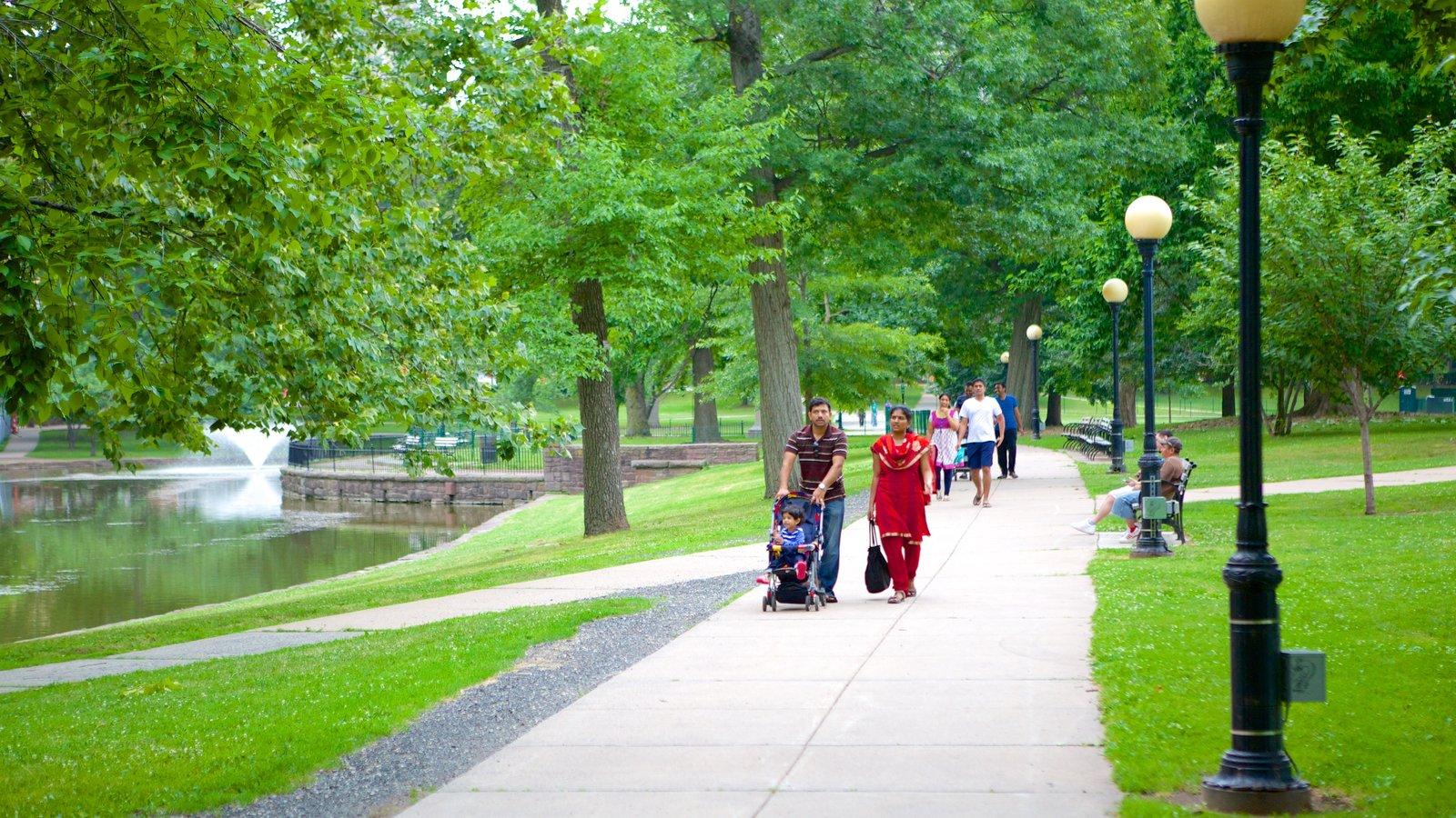 Bushnell Park caracterizando um jardim e escalada ou caminhada assim como uma família