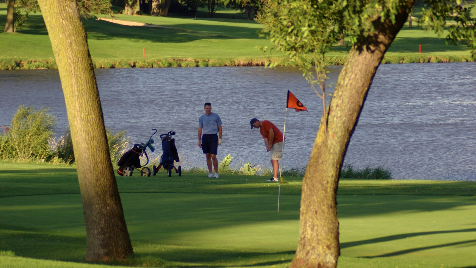Rockford featuring a lake or waterhole and golf as well as a small group of people