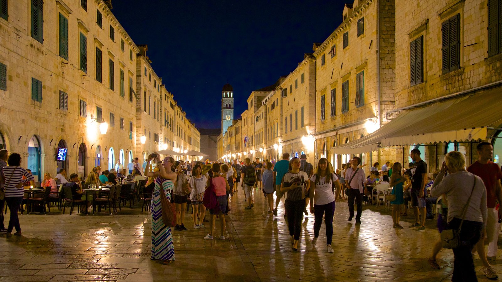 Stradun which includes heritage architecture and night scenes as well as a large group of people