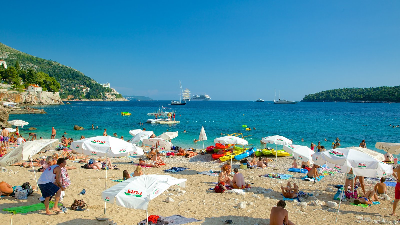 Banje Beach featuring a beach as well as a large group of people