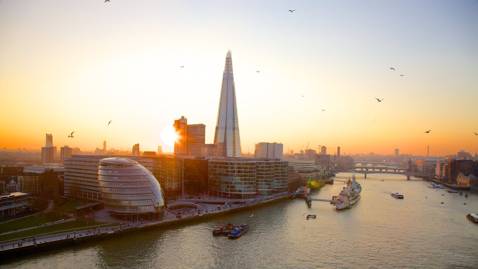 Tower Bridge which includes a sunset, a bay or harbor and modern architecture