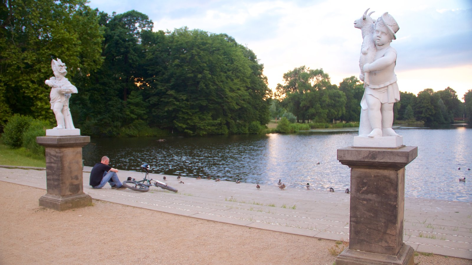 Schloss Charlottenburg showing a statue or sculpture and a lake or waterhole as well as an individual male