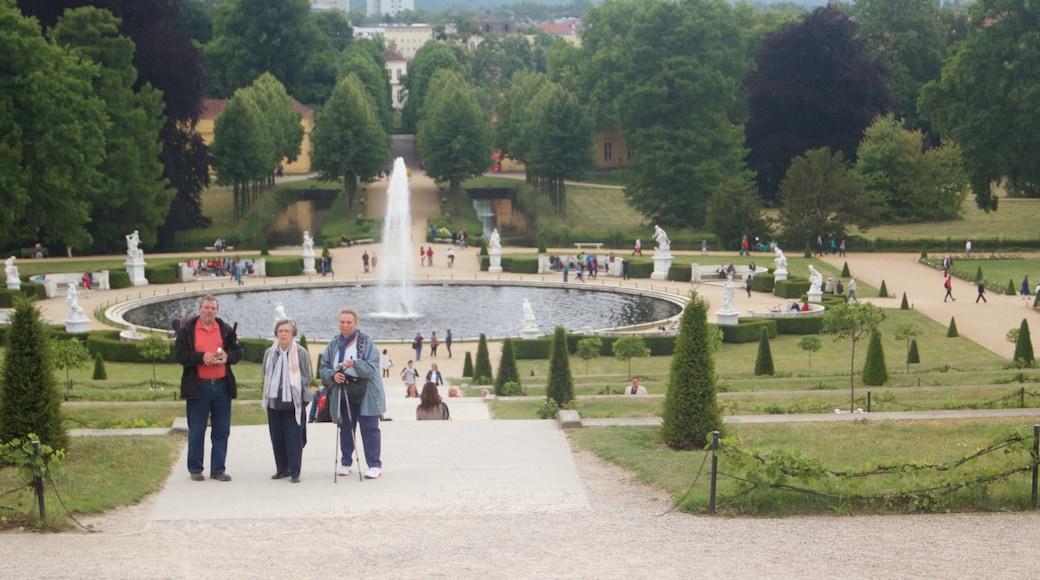 Palais de Sanssouci qui includes fontaine et château ou palais aussi bien que petit groupe de personnes