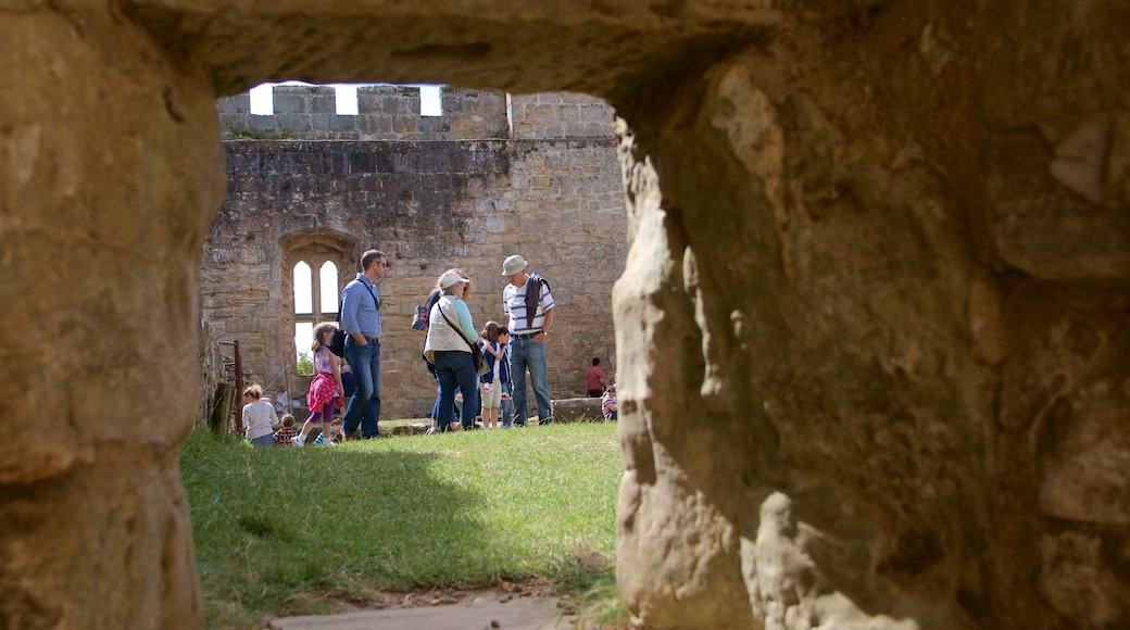 Bodiam Castle showing château or palace and heritage elements as well as a small group of people