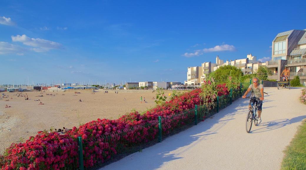 Playa de Minimes ofreciendo una playa de arena y flores y también un hombre