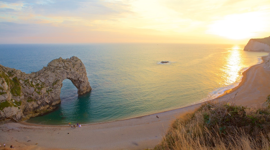 Durdle Door showing a bay or harbour, rugged coastline and a sunset