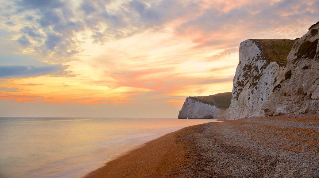 Durdle Door which includes rugged coastline, a pebble beach and a sunset