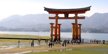 Hiroshima featuring heritage elements and a lake or waterhole as well as a large group of people