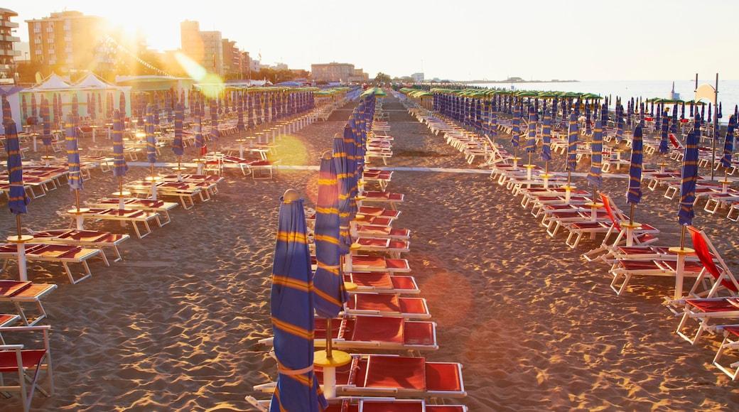 Pesaro montrant plage de sable, coucher de soleil et hôtel ou complexe de luxe