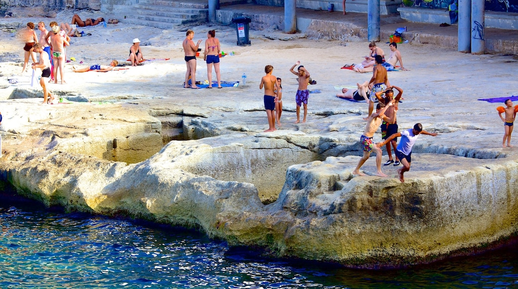 Sliema showing rugged coastline and swimming as well as a large group of people