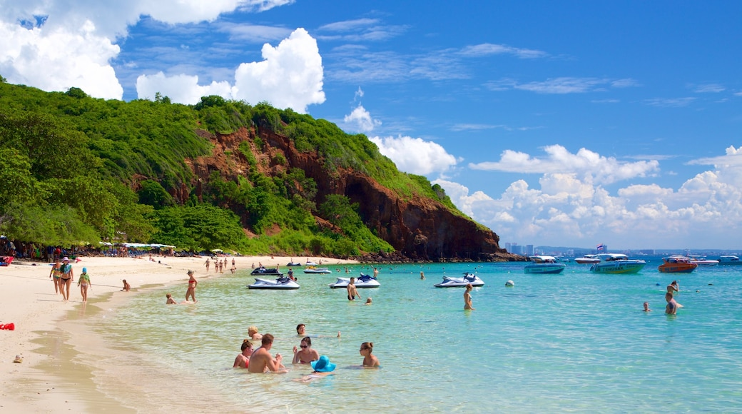 Nual Beach featuring a bay or harbor and swimming as well as a large group of people
