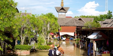 Pattaya Floating Market featuring a river or creek and boating as well as a large group of people