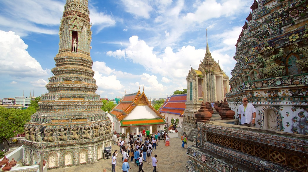 Wat Arun which includes a temple or place of worship as well as a large group of people