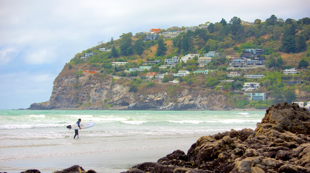 Sumner Beach showing rugged coastline, surfing and a coastal town