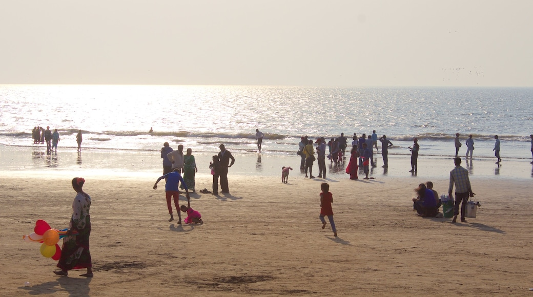 Juhu Beach featuring a sunset and a beach as well as a large group of people