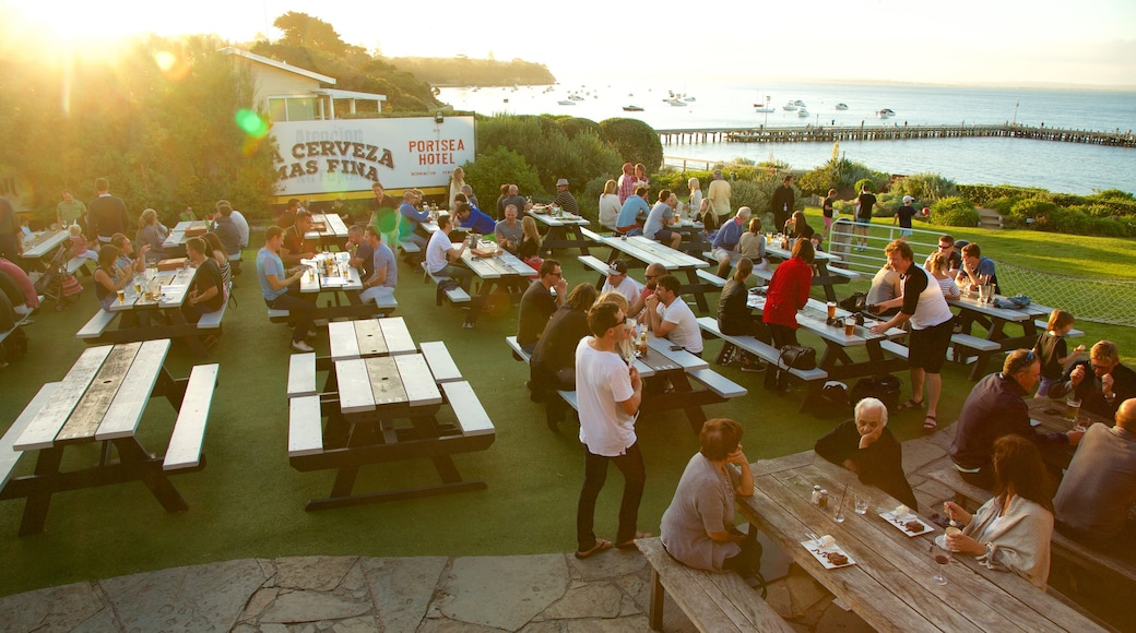 Portsea showing a sunset and outdoor eating as well as a large group of people