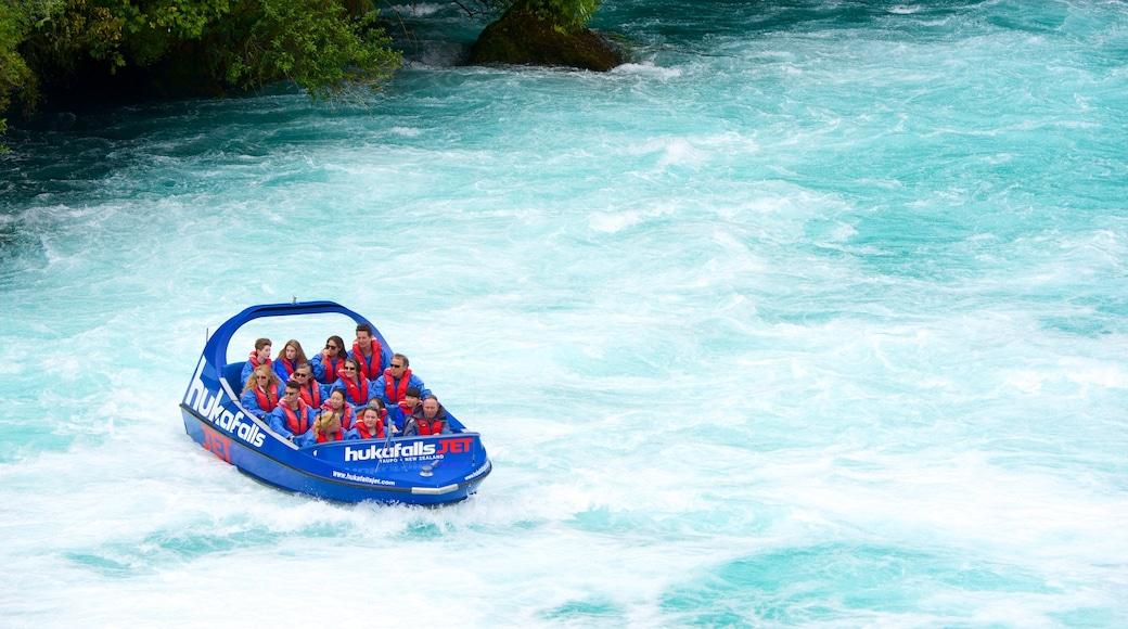 Huka Falls which includes a river or creek and boating as well as a small group of people