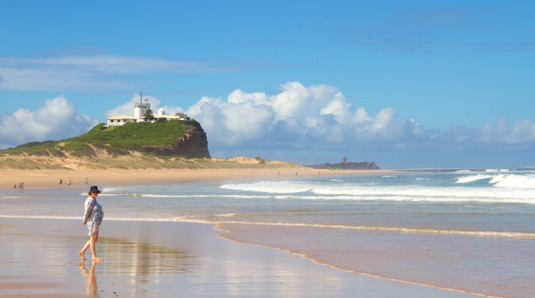 Nobbys Head Beach featuring a sandy beach and a lighthouse as well as an individual female