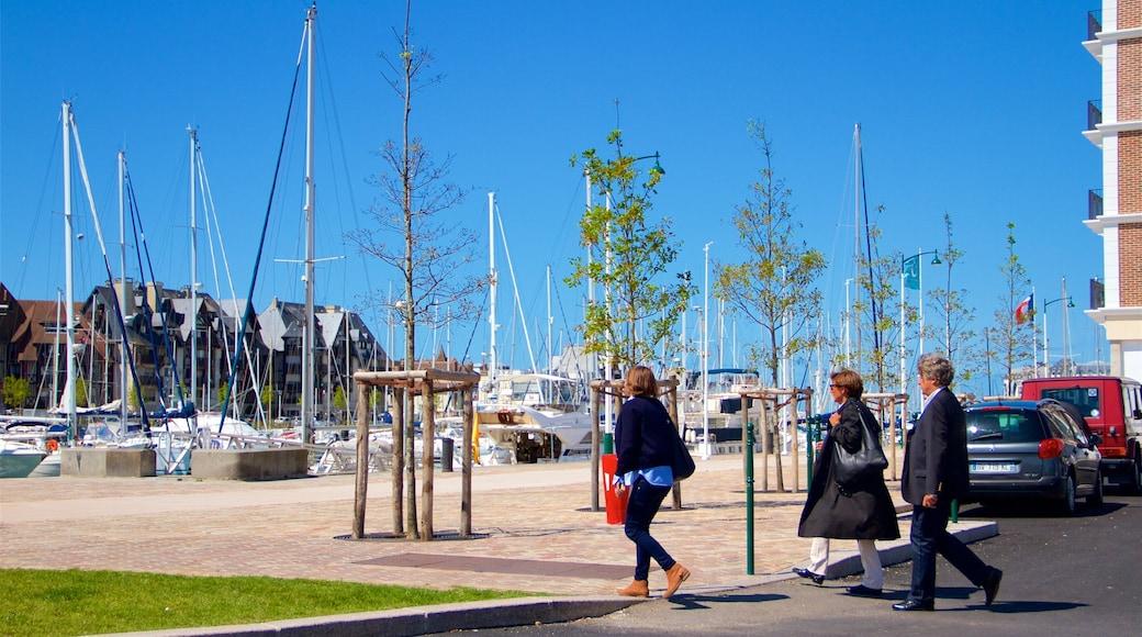 Deauville montrant marina aussi bien que petit groupe de personnes