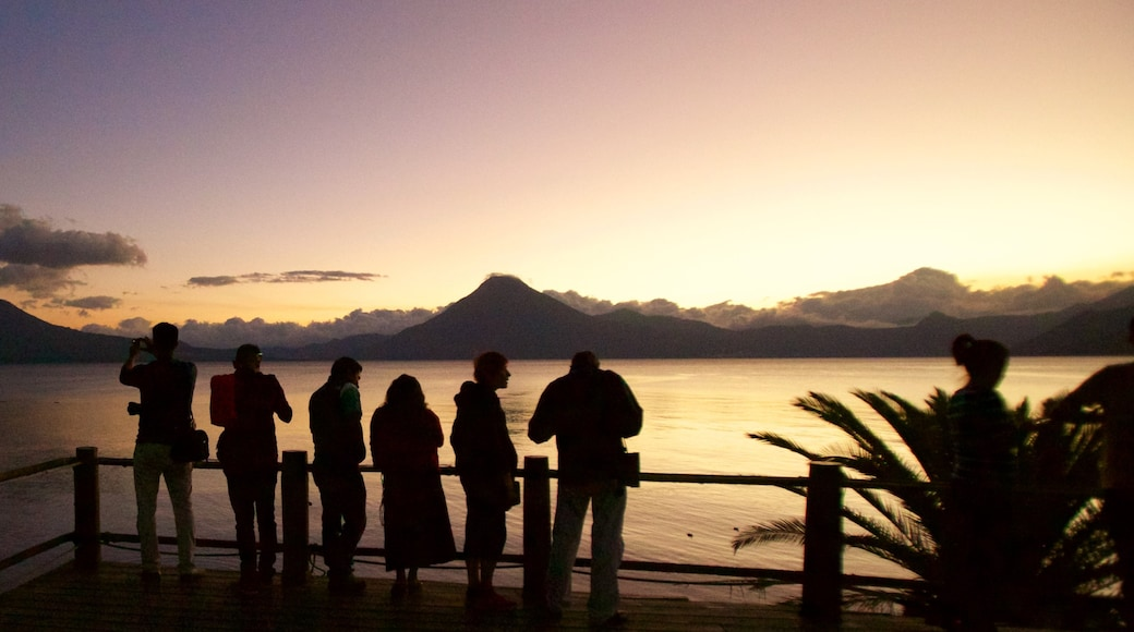 San Pedro Volcano featuring a sunset and general coastal views as well as a small group of people