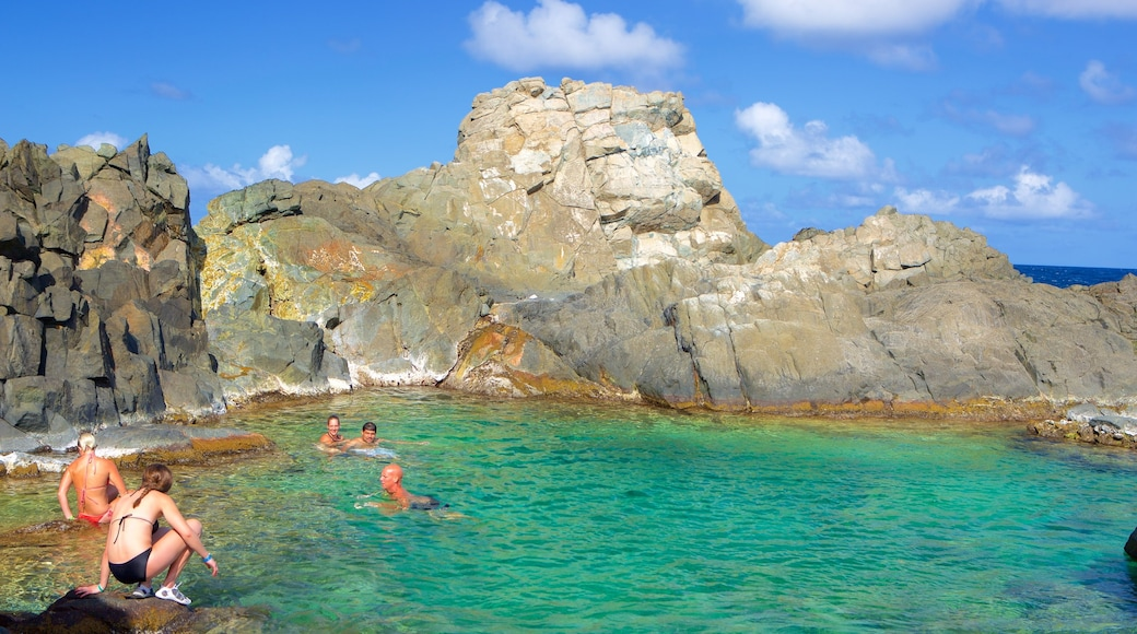 Conchi Natural Pool which includes general coastal views as well as a small group of people
