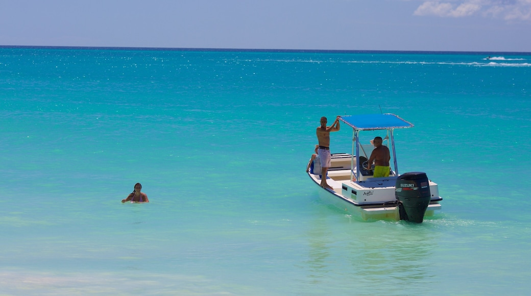 Eagle Beach featuring boating as well as a small group of people