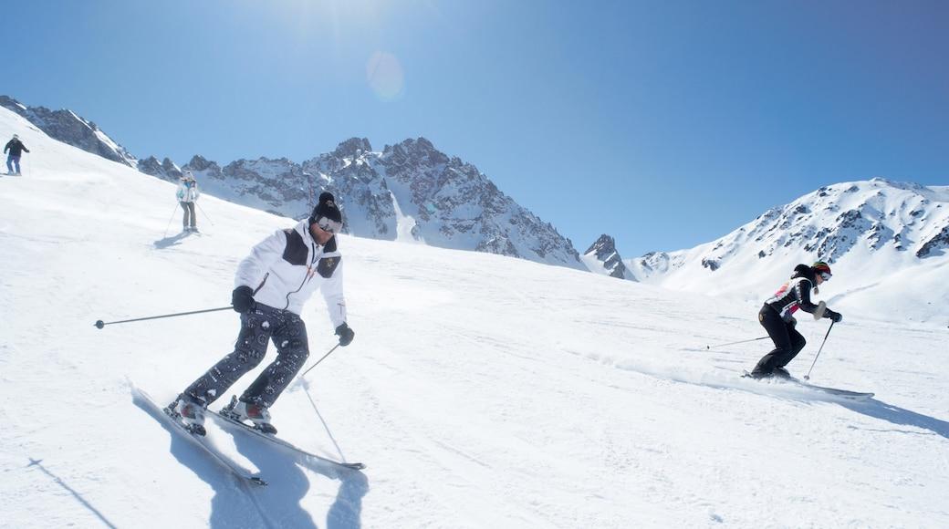Domaine skiable de Courchevel montrant neige et ski aussi bien que petit groupe de personnes