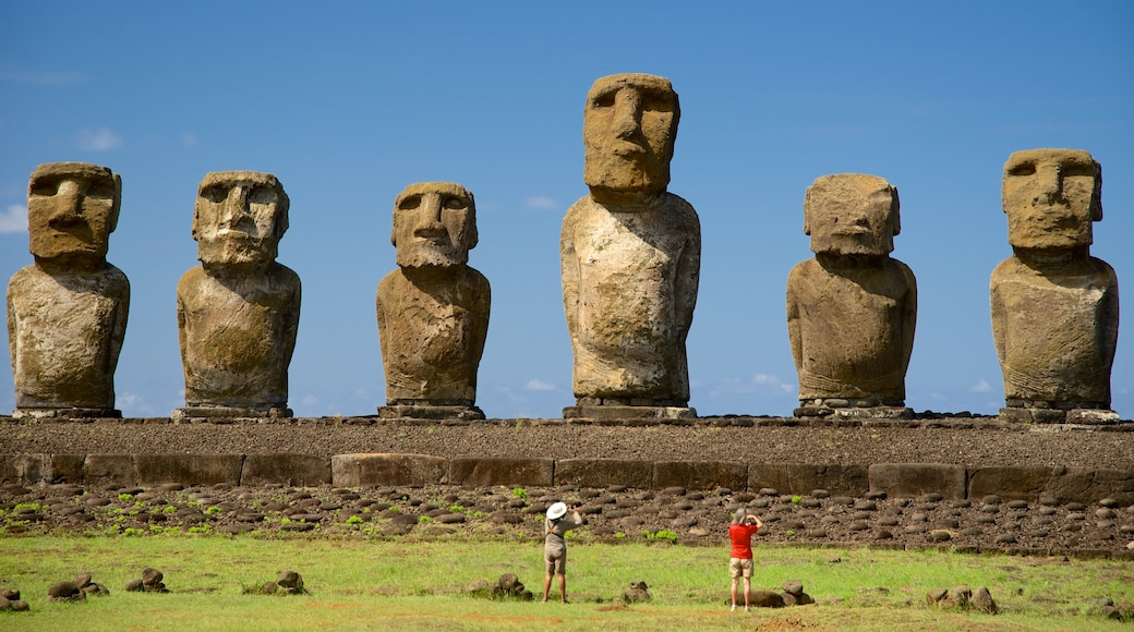 Ahu Tongariki featuring a statue or sculpture and heritage elements as well as a small group of people