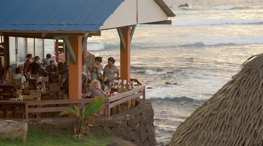 Hanga Roa featuring dining out and general coastal views as well as a small group of people