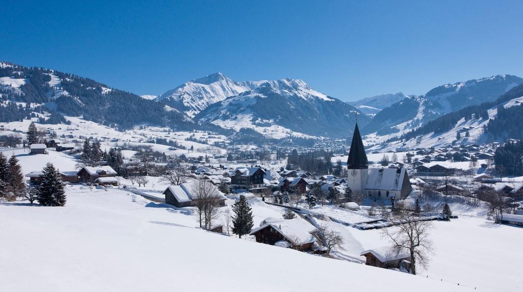 Estación de esquí de Gstaad que incluye una pequeña ciudad o pueblo, nieve y montañas