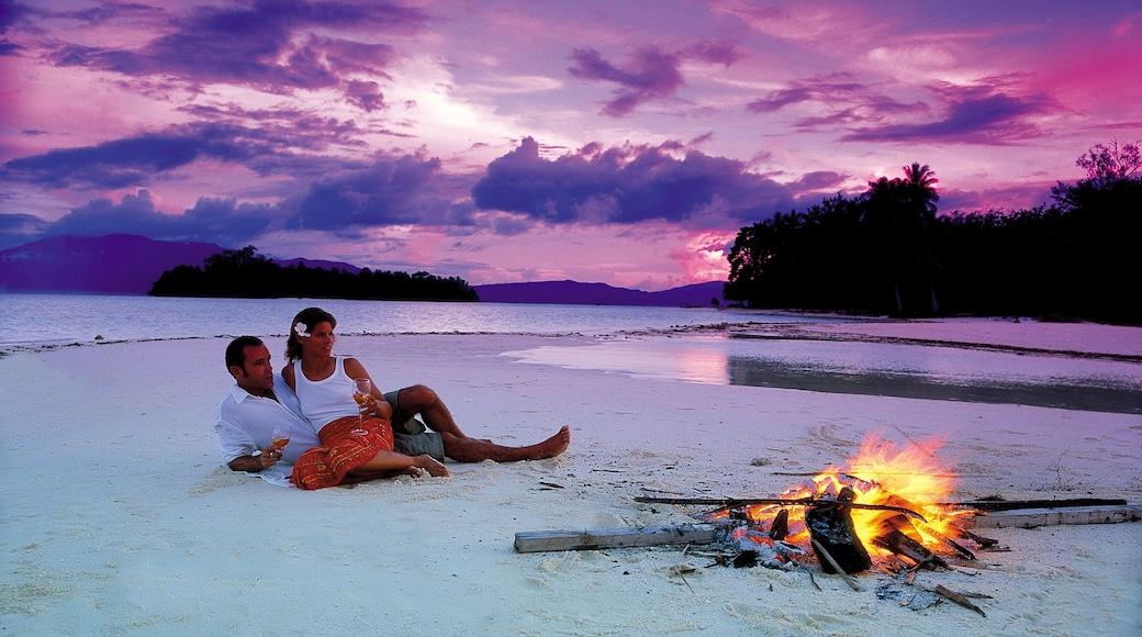 Islas Salomón que incluye una puesta de sol y una playa de arena y también una pareja