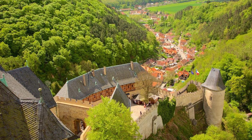 Karlstejnin linna johon kuuluu metsänäkymät, linna ja pieni kaupunki tai kylä